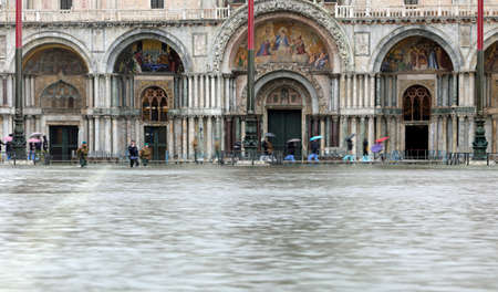 water in Saint Mark square and people on the footbridges in Venice in Italy