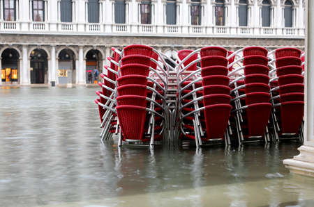 red chairs of a restaurant in Venice Italy with high water called Acqua Alta in Italian Language