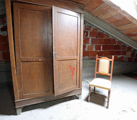Viejo armario polvoriento en el ático con una silla de madera sin gente Foto de archivo