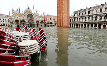 Saint Mark square called Piazza San Marco in Italian language during the high tide in Venice and many red chairs of an alfresco cafe
