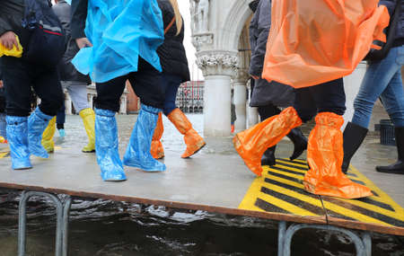 Feet of people with rain coats and plastic leggings on the footbridge in Venice in Italy during the flood