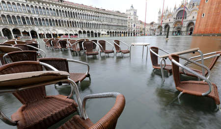 chairs and small tables of sidewalk cafe in Venice Italy with high water called ACQUA GRANDA in Venetian language Stock fotó