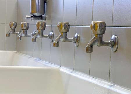 rubinetti a lunga fila nel grande lavello della scuola senza bambini e il distributore di sapone
