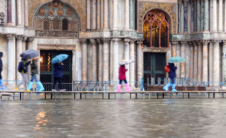 People walk on the footbridge in front of Basilica of Saint Mark in Venice Italy during the high water