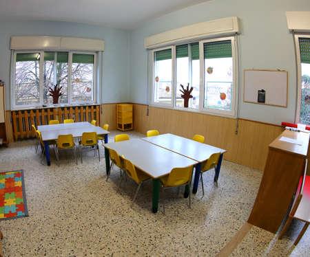 dentro de un aula escolar sin niños con sillas de plástico de colores y mesas pequeñas