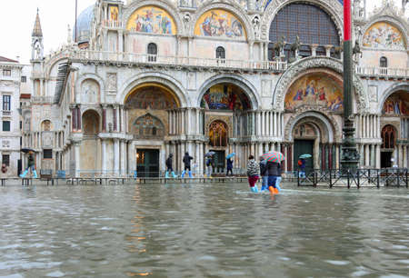 Basilica of Saint Mark in Venice in Italy with high tide and the walkway with people