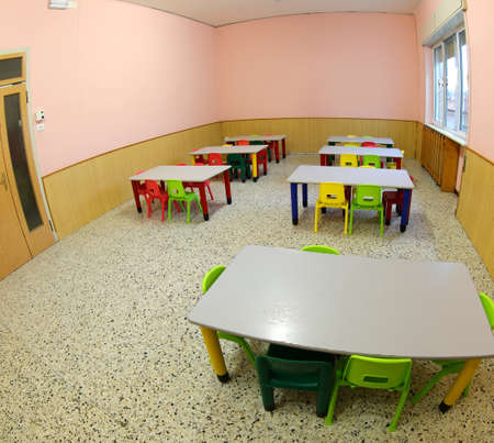 school classroom with colorful plastic chairs and small tables without children