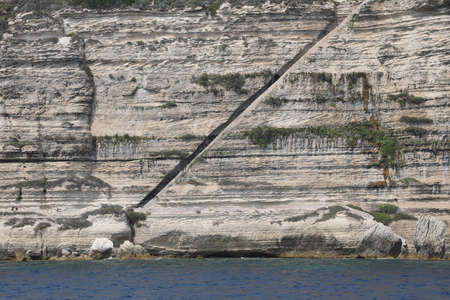 Long stairway on the rock in Bonifacio Town in Corsica and the mediterranea Sea in summer