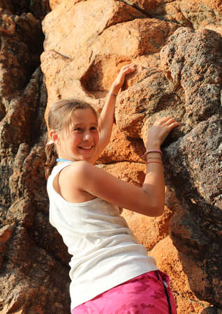 young smiling little girl as she climbs the red rock of the mountain in the summer