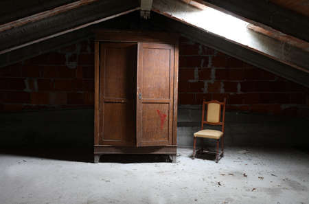 old wooden wardrobe and a vintage chair in the dusty attic without people Stock Photo