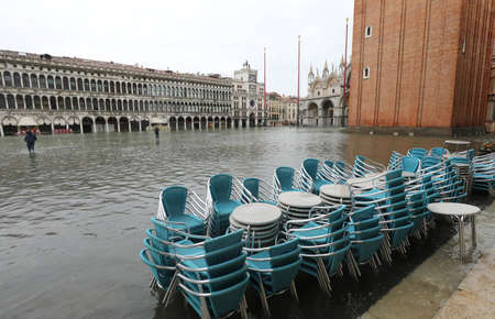 chairs of a sidewalk cafe in Saint Mark Square in Venice Itay with high tide and the bell tower in background Banco de Imagens - 134774638