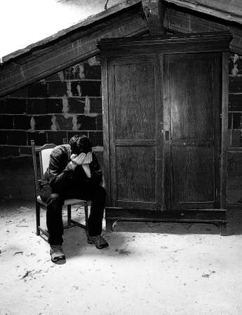 sad man in the attic and an old wooden wardrobe with black and white toned effect