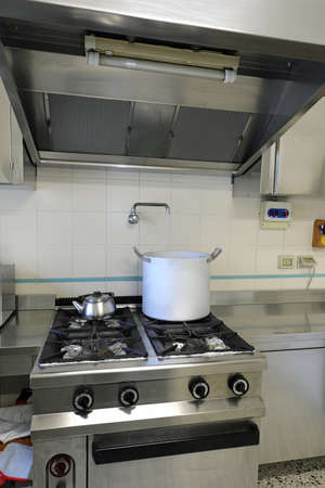 Industrial Kitchen with large industrial stove with aluminum pot on the fire