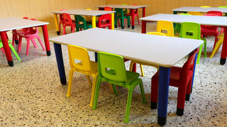 refectory hall with colorful plastic chairs and small tables in the nursery without children
