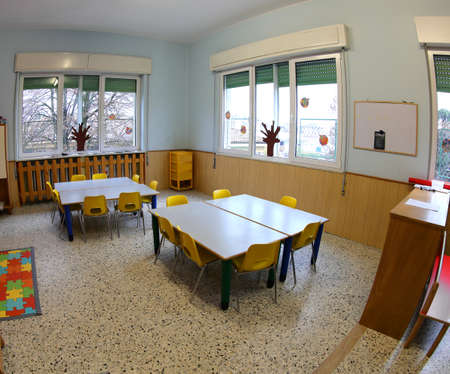 inside a school classroom without children with colorful plastic chairs and small tables