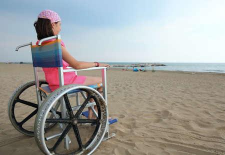 Niño discapacitado sentado en una silla de ruedas mirar el mar desde la playa