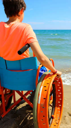 young perosn on a wheelchair looks at the sea in summer