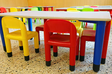 plastic chairs and small tables in a refectory room of a kindergarten for children