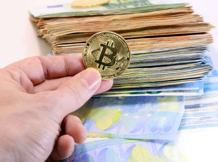 hand with a bitcoin coin and many banknotes Foto de archivo
