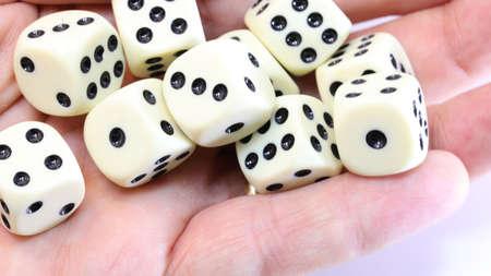many white dice on the hand of a man 版權商用圖片