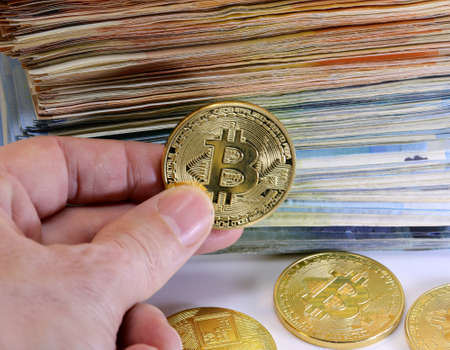 hand holding bitcoin coin and a pile of money on the background