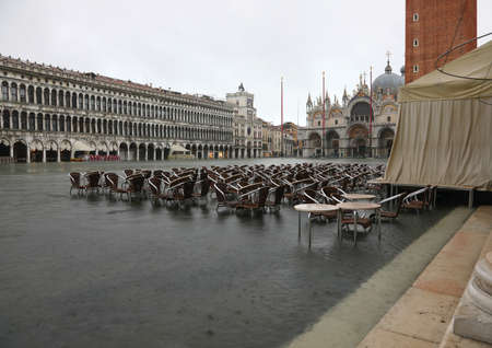 alfresco cafe underwater in Saint Mark Square in Venice Italy during the high tide Banco de Imagens