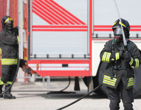 fireman with hose hydrant in action and fire engine on background