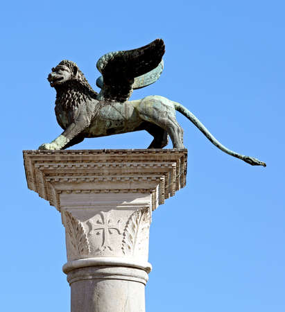 winged lion symbol of Venice called LEONE ALATO in Italian Language in Italy over a white column in Piazza San Marco