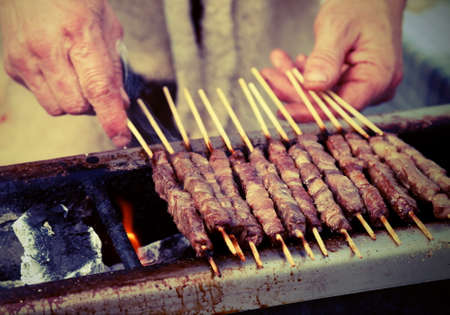 Elderly man while cooking skewer called ARROSTICINI in Italian language with old toned effect Archivio Fotografico