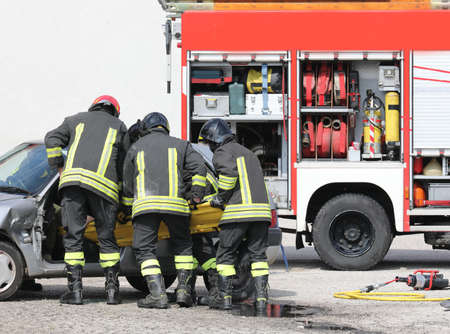 truck and the brave firefighters with the stretcher extract the injured from the car after the road accident