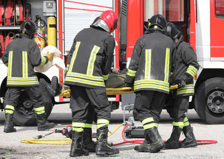 firemen in uniform with the stretcher and the injured after the road accident