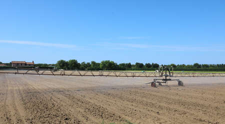 large industrial automatic irrigation system in a cultivated field during an arid summer