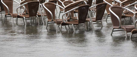 many brown chairs of a venetian alfresco cafe with water during the tide