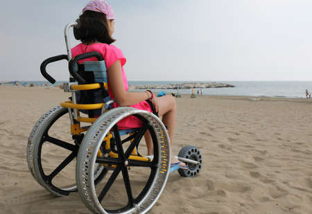 special wheelchair with big wheels in aluminium and a little girl in summer