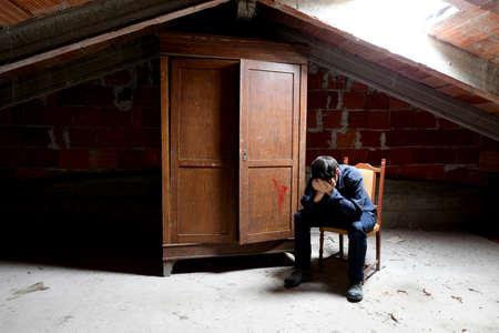 sad man in the attic and an old wooden wardrobe Archivio Fotografico