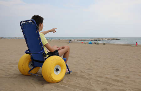 young boy on the special wheelchair with big inflatable wheels to go on the sea in summer