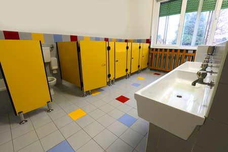 inside a wide bathroom with yellow doors of a kidergarten Stock Photo