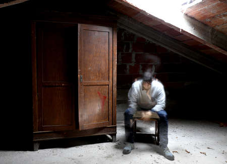 desperate spectral man on the chair in the attic with wooden wardrobe Banque d'images