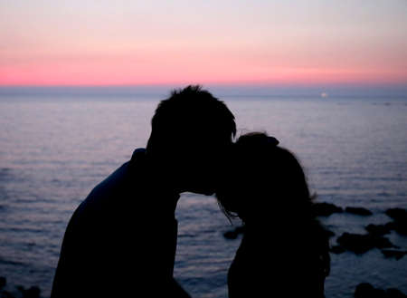 happy lovers lovingly kissing each other during a romantic sunset by the clear sea Imagens