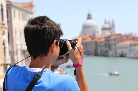 Young photographer in Venice in Italy with digital camera and the Grand Canal on background