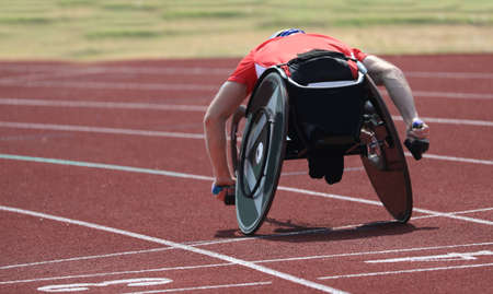 muscular athlete runs on the wheelchair in the running track