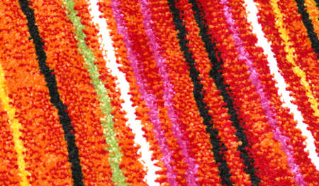detail of an inexpensive chenille rug with horizontal stripes colored with bright colors
