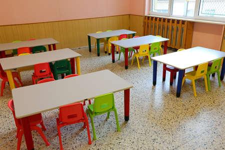 sillas y mesas pequeñas de una clase sin niños que estaban en casa debido a la epidemia de gripe Foto de archivo