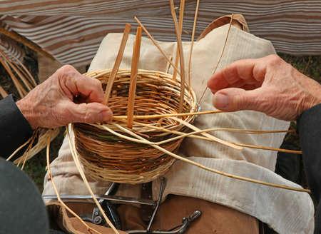 hands of an elderly gentleman weave a wicker basket