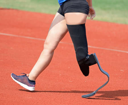 Paralympic athlete with prosthesis in the left leg in the running track during the race Фото со стока
