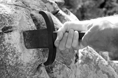 Legendary Sword in the stone and the hands in black and white effect
