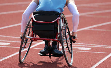 Paralympic athlete in a wheelchair with a paralysis in the legs while running fast on the running track during the race