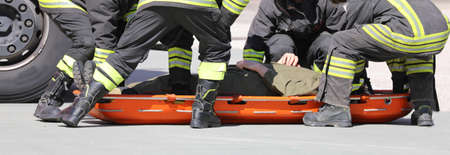 Teamwork of four firefighters and a stretcher with injured person