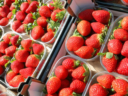 small baskets of freshly picked red strawberries for sale at the greengrocer Banque d'images