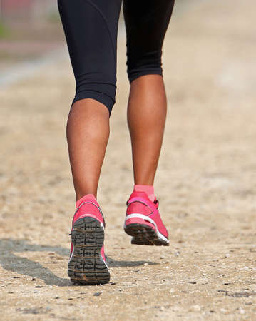 legs of a african girl during race with pink shoes